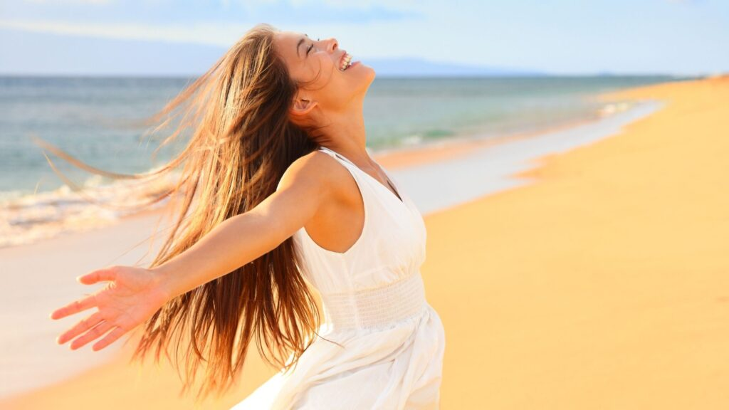 a stress free woman on the beach with her arms open wide