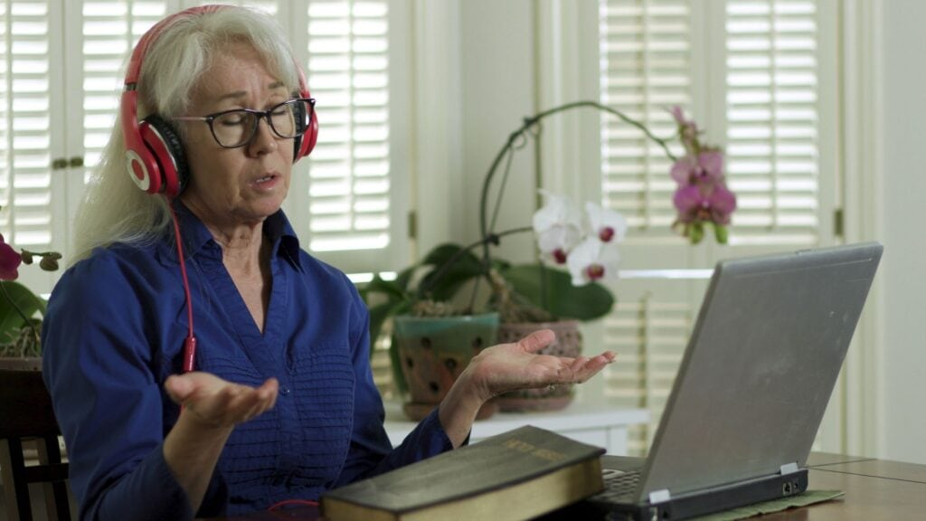 mature woman worshipping while watching church service on her computer