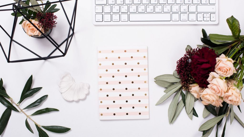 white keyboard, bold polkadot notebook and some flowers on a desk