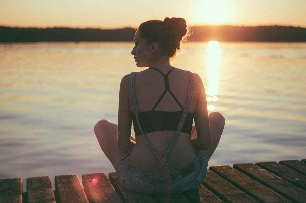 woman sitting on a dock overlooking the lake at sunset