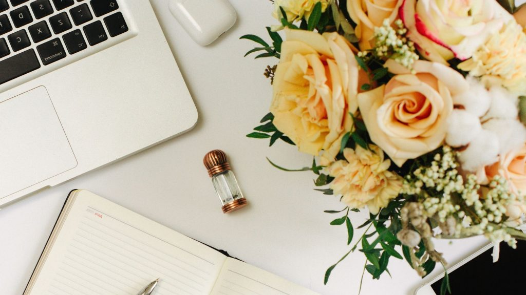gold roses next to a silver laptop and notebook laying on a desk