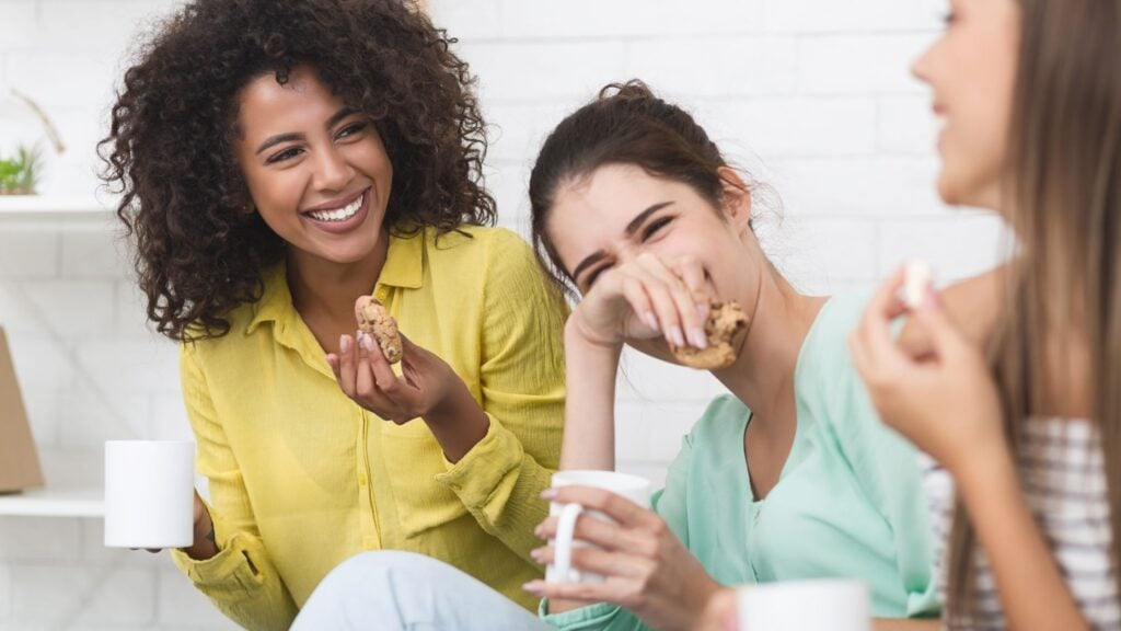 3 women laughing and drinking coffee