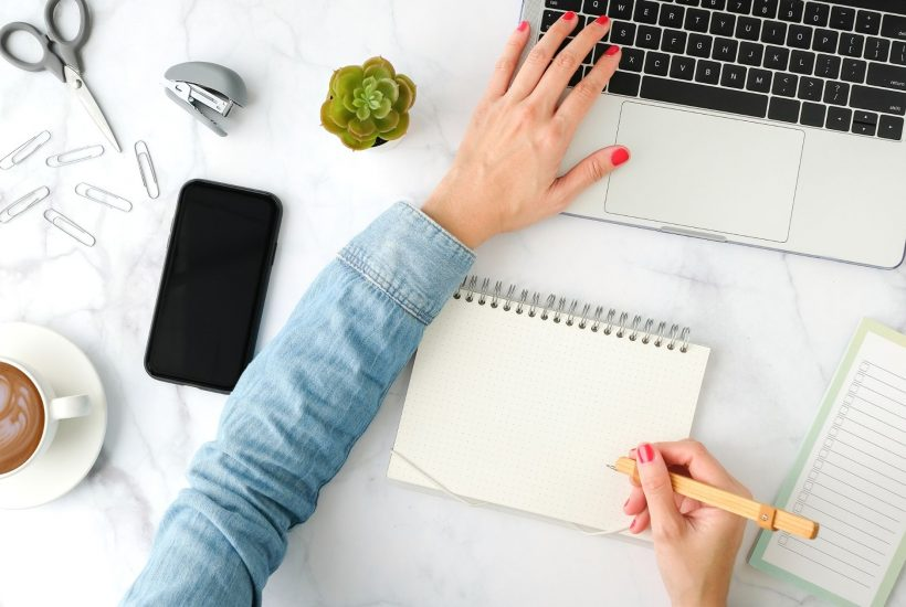 a woman's hand reach across the desk to her laptop while writing on a notepad with the other hand
