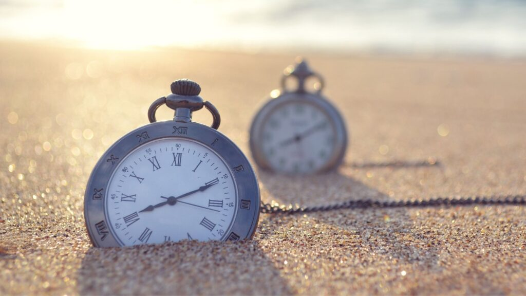 two antique stopwatches laying in the sand on a beach