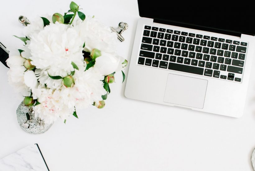 white flowers next to a silver laptop on a white desk