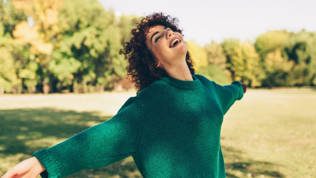 happy woman with a green sweater smiling with arms spread wide out in nature