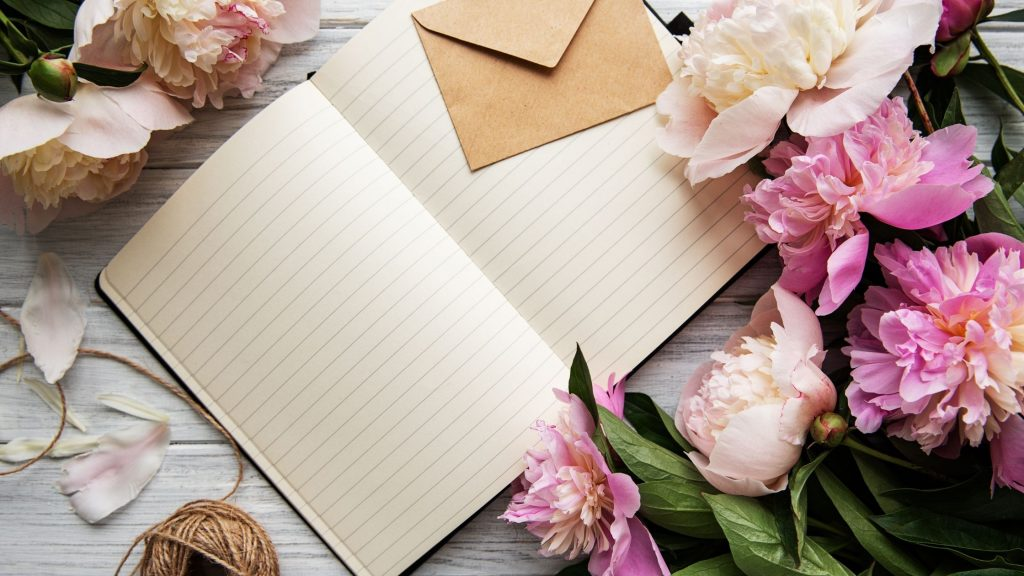 notebook on a desk with pink flowers