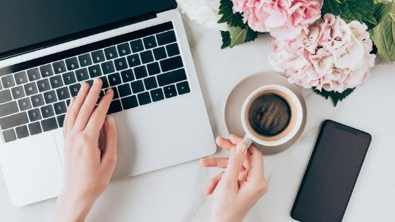 laptop next to a cup of coffee and pink flowers