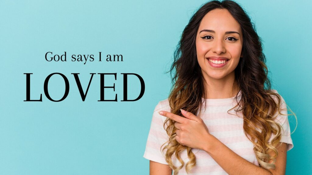 woman pointing to a sign that says God says I am loved