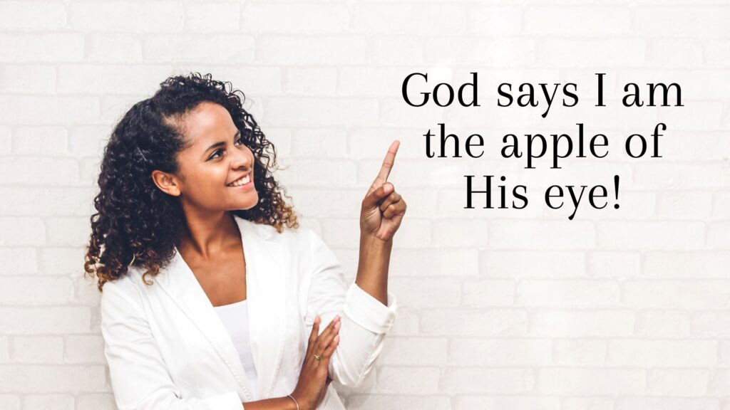woman pointing to a sign that says god says I am the apple of his eye