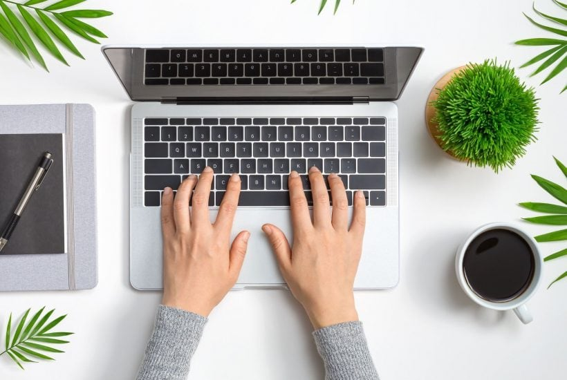 hands typing on a laptop next to a cup of coffee and several green house plants