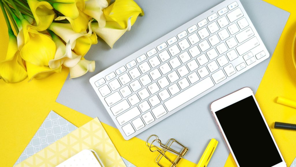 yellow desktop with a white keyboard, cell phone and yellow accessories