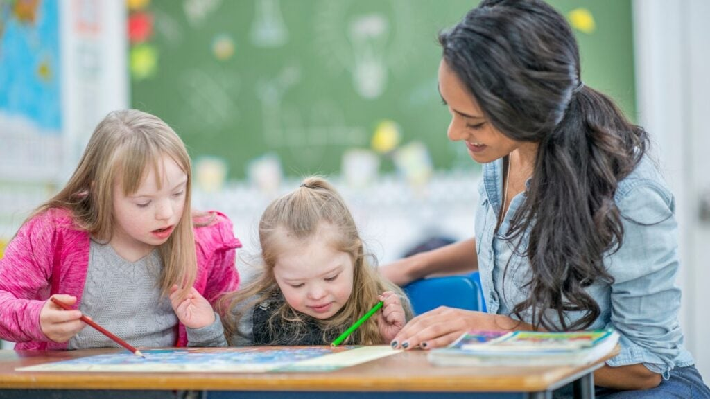 special needs teacher giving instruction to 2 students