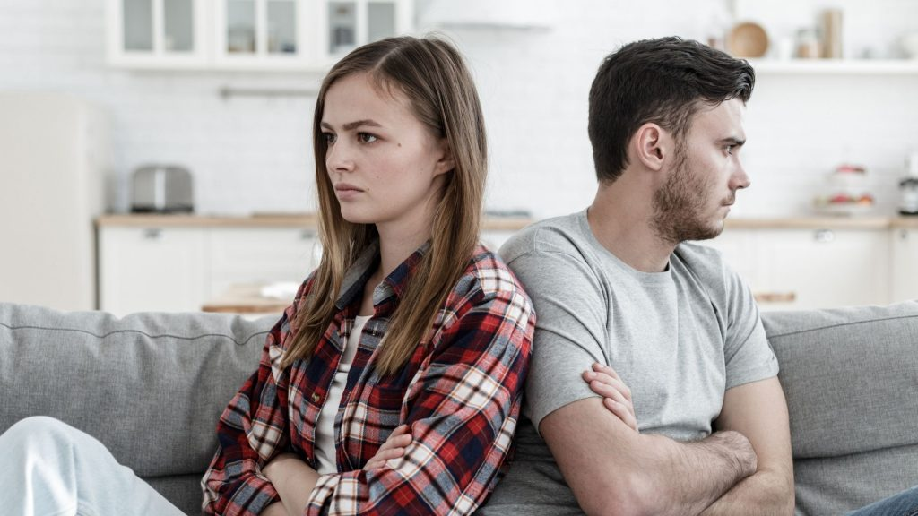 unhappy man and woman sitting with their backs to each other on the couch