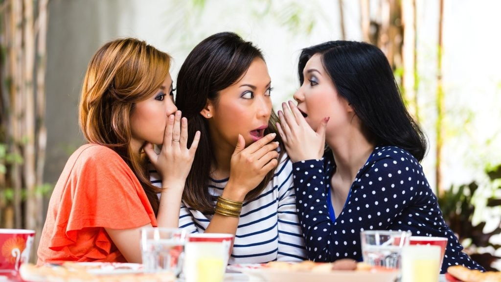 three women sitting at a table sharing gossip