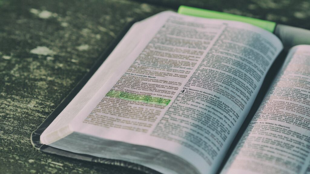 an open bible laying on a table with a verse of scripture highlighted in yellow