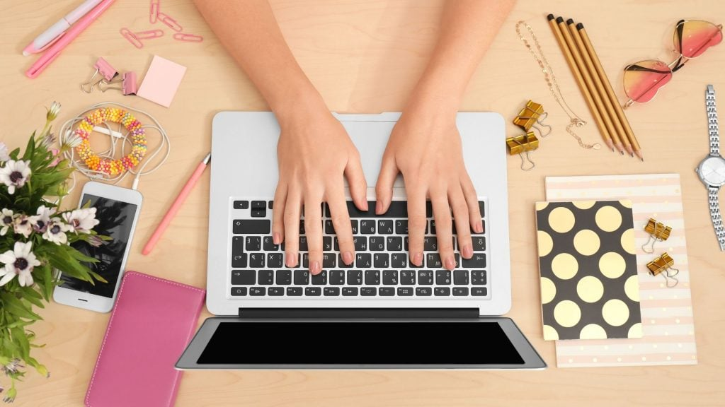lady's hands typing on a laptop on her desk