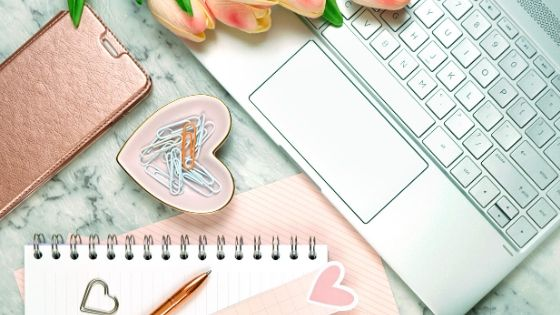 laptop on a desk with a pink notebook and pink accessories