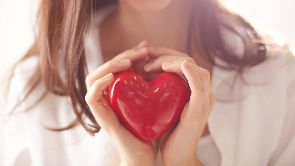 woman with her hands cupped together around a red heart