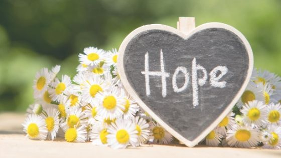 heart shaped chalkboard with the word hope written on it and flowers in the background