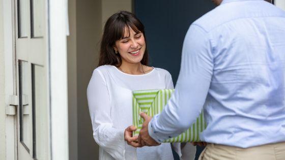 man handing woman a Christian housewarming gift