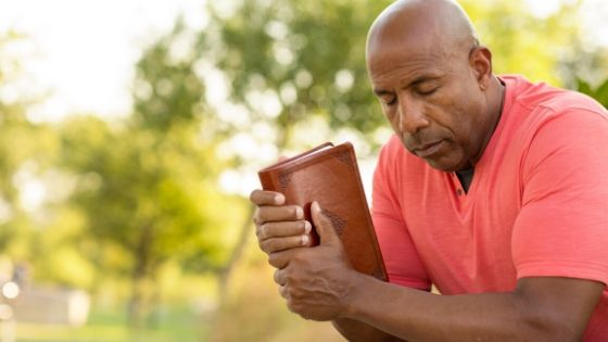 african american mad holding a men's bible