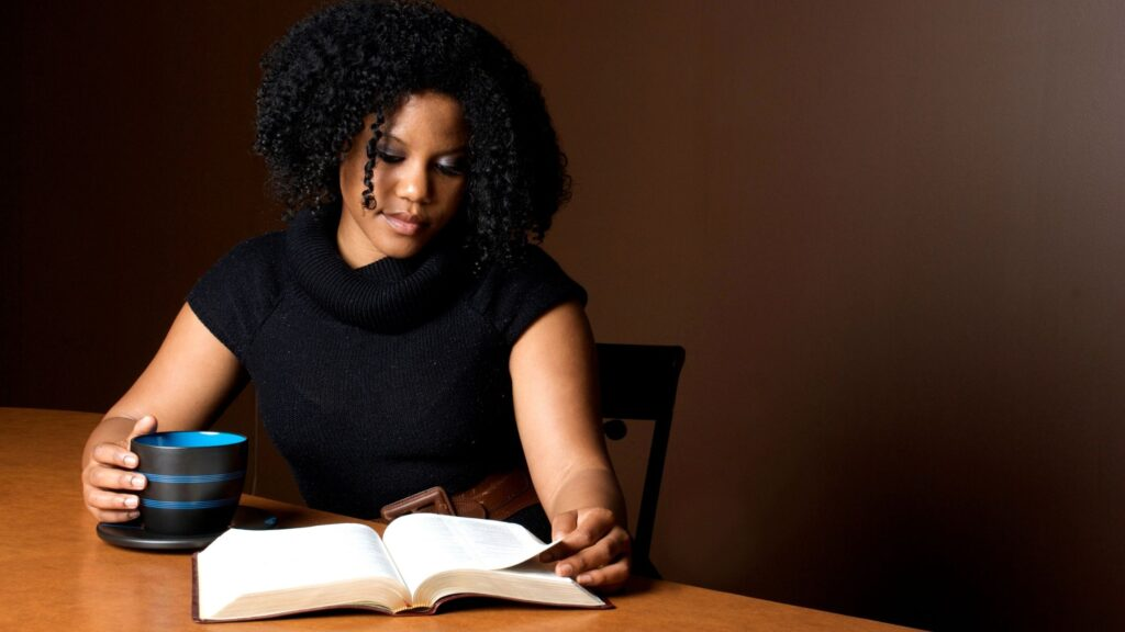 woman sitting at a table reading her Bible and drinking coffee