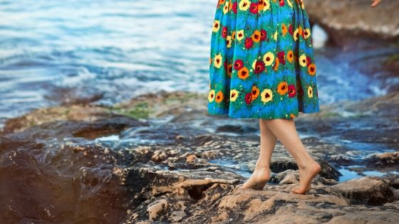 woman's feet walking along the edge of the water wearing a floral dress