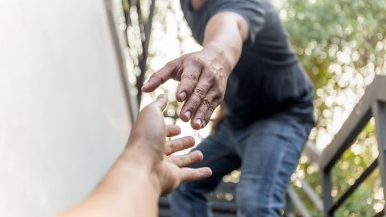 man extending a hand out to help someone