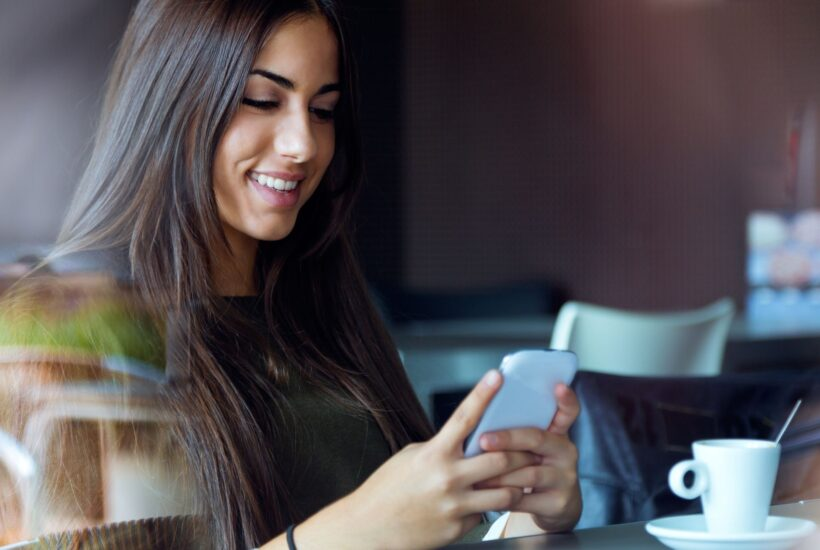 woman sitting in a coffee shop reading from her daily devotional app