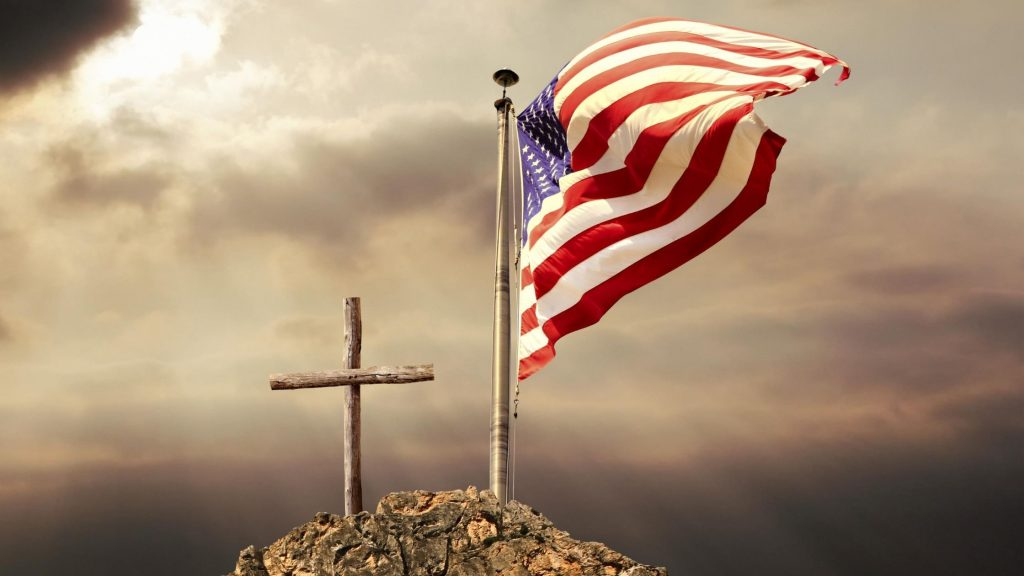 american flag next to a cross on the top of a mountain