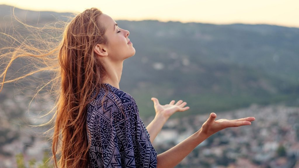woman praying with hands to the sky