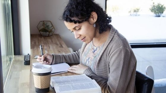 woman reading the bible and taking notes on a notepad, next to a cup of coffee