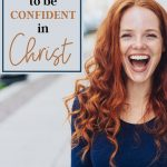 happy red headed woman next to a sign that says my confidence comes from christ