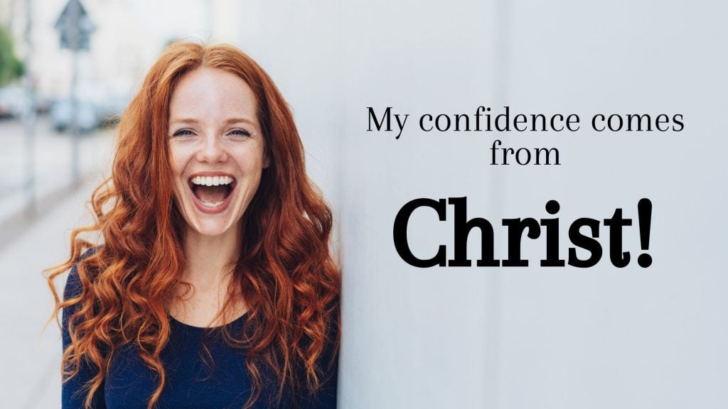 happy red-headed woman next to a sign that says confidence in christ