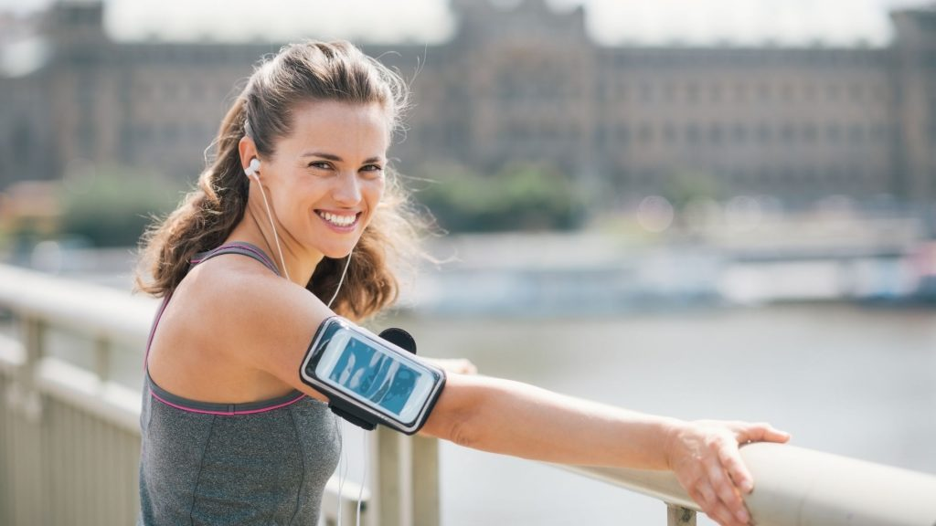woman-standing-on-bridge-wearing-an-armband-with-her-ipod-and-workout-music