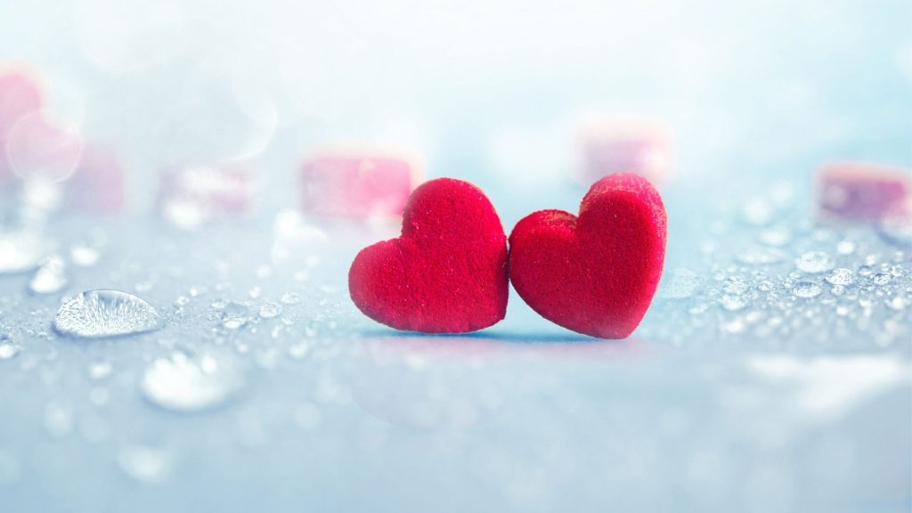 2-red-hearts-on-a-light-blue-table-with-rain-drops-all-around
