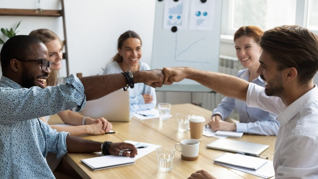 group of office workers encouraging each other