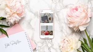 marble table with pink flowers and an iphone with a free online bible study showing