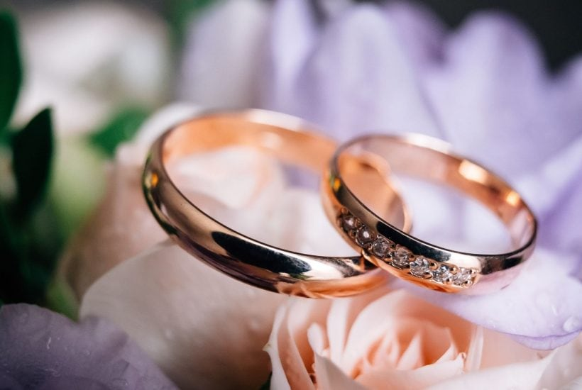 2 gold wedding bands laying on a bed of pink roses
