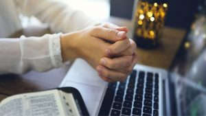 christian-blogger-sitting-at-her-desk-with-hand-together-over-a-laptop-and-next-to-a-bible