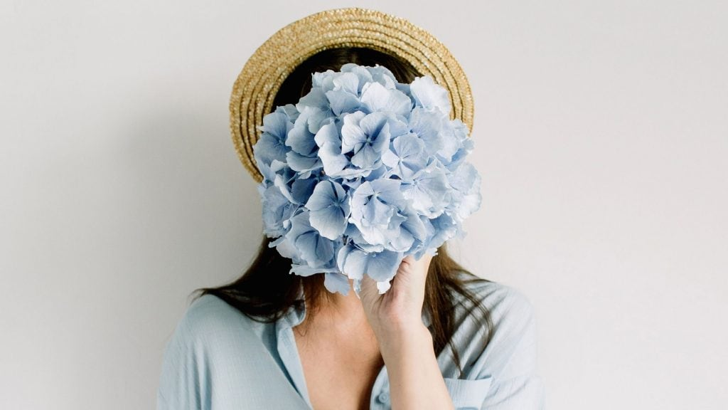 woman holding blue flowers in front of her face