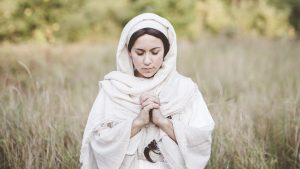 woman in a white robe praying in a field