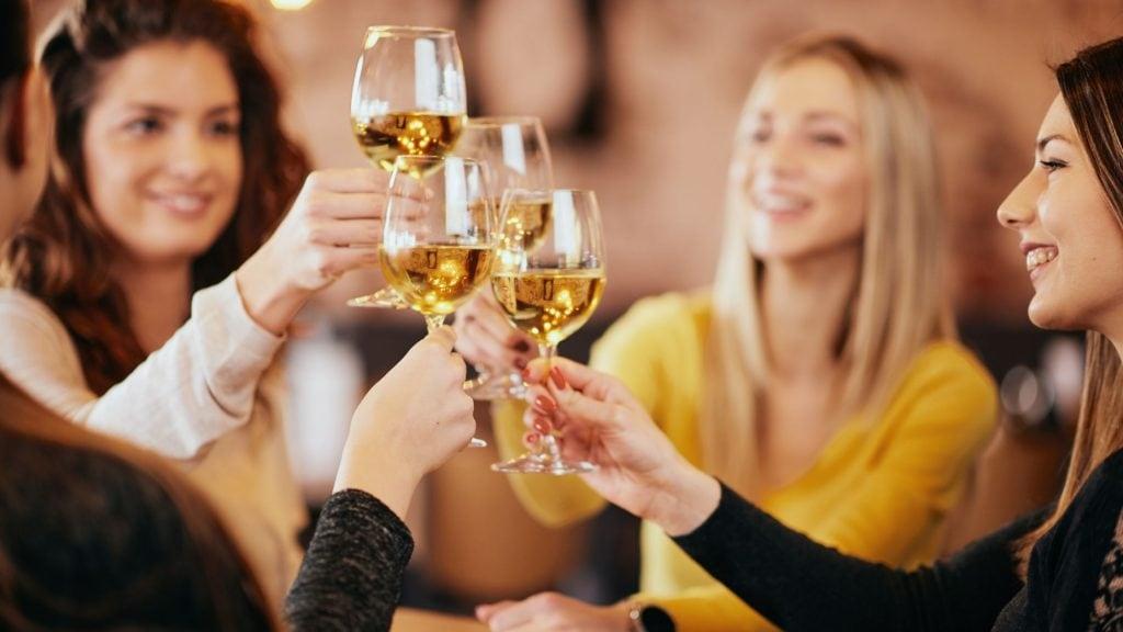 women toasting wine glasses over dinner