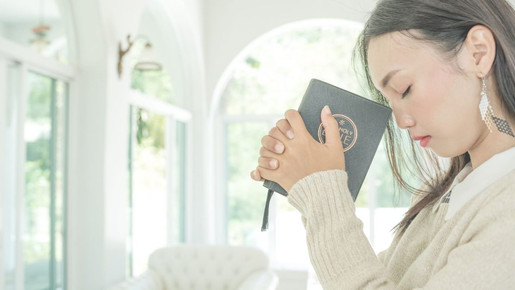 woman praying as she holds her bible close to her head