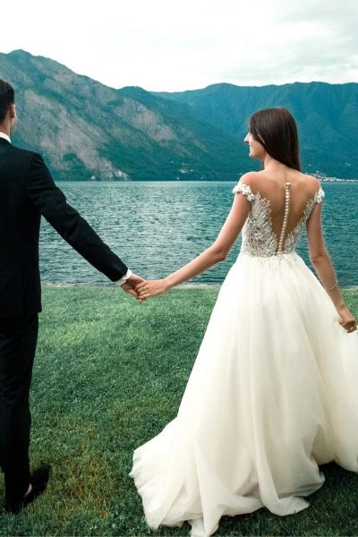 newly married couple looking out over the lake at the mountains