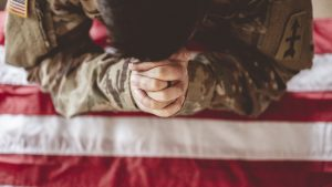 American soldier mourning and praying with the American flag in front of him