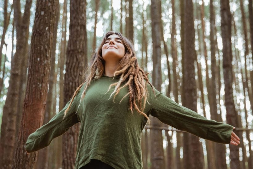 woman standing in the forest with her arms spread wide looking to the sky in prayer