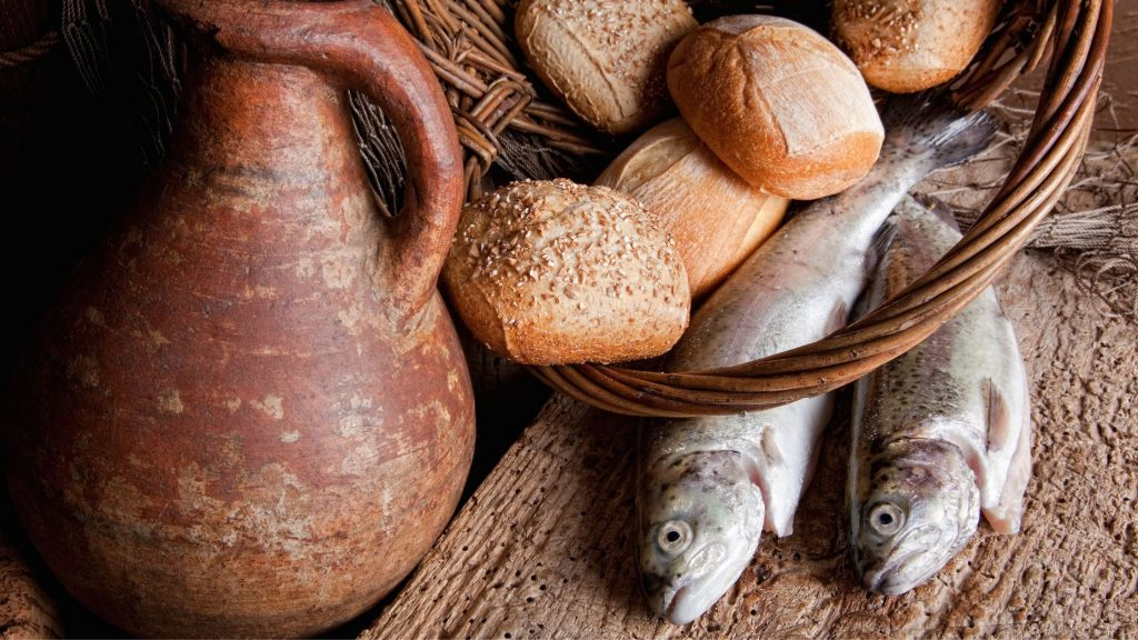 basket of bread next to 2 fish and a pot