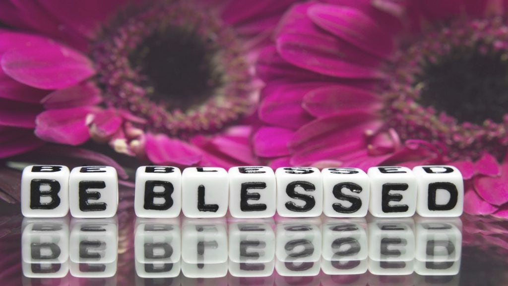 white blocks with letters spelling be blessed on a table with flowers in the background